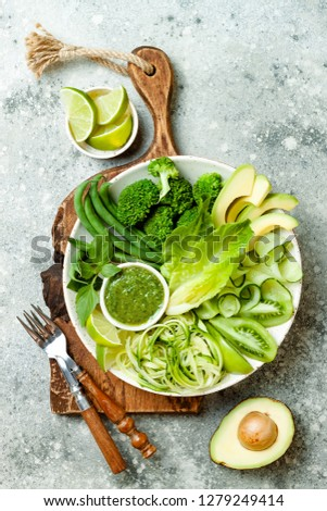 Vegan, detox Buddha bowl with avocado, zucchini noodles, green beans, spiralized cucumber, tomatoes, broccoli, lime and pesto sauce. Top view, grey concrete background