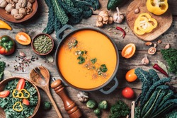 Vegan diet. Autumn harvest. Healthy, clean food and eating concept. Zero waste. Pumpkin soup with vegetarian cooking ingredients, wooden spoons, kitchen utensils on wooden background. Top view
