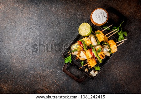 Vegan diet food, Grilled cheese and vegetables kebab, indian style Paneer Tikka, with white sauce and lime, on dark concrete background, copy space top view