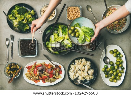 Vegan dinner table setting. Healthy dishes in plates on table. Flat-lay of vegetable salads, legumes, beans, olives, sprouts, hummus and woman hands mixing ingredients on plate, top view