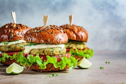 Vegan falafel burger with vegetables and sauce, dark background. Healthy food concept.