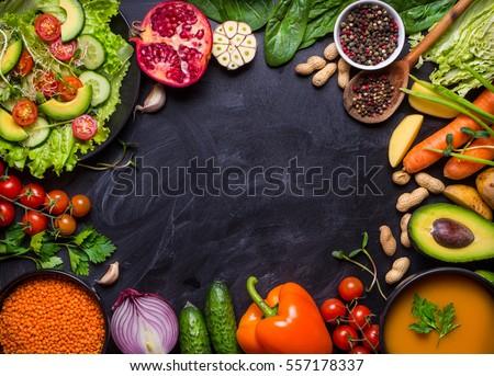 Vegan food and dishes. Pumpkin soup, salad, vegetables, fruits, lentils on rustic black chalk board background. Healthy, clean eating concept. Vegan or gluten free diet. Space for text. Vegan dinner
