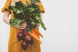 Vegan food organic vegetables woman giving beet and carrot bunch healthy eating lifestyle eco bio veggies from garden home grown plant based diet nutrition