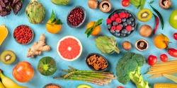Vegan food panorama. Healthy diet concept. Fruits, vegetables, nuts, legumes, mushrooms, shot from the top on a blue background, a flatlay