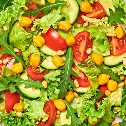 Vegan greens salad, chickpeas, lettuce, arugula, cherry tomatoes. Home made vegetarian green salad. Diet, vitamin food concept. Tasty veg mix leaves salad background, closeup, macro