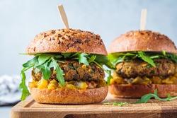 Vegan lentil burger with arugula, mustard sauce, fresh vegetables and sweet potato fries on a wooden board. Vegan food concept.