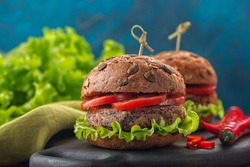 Vegan lunch. Veggie burger made from quinoa, beans, peanut sauce, green salad, hot peper and tomatoes. Dark blue background.