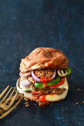 Vegan messy burger with mashed bean patty, with tomatoes, onions, cheese and melted cheese, on a blue background with brass cutlery. Restaurant, cafe, kitchen, menu, veganism concepts.