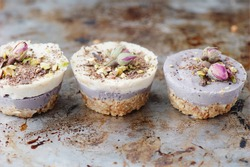 Vegan mini cheesecakes  with blueberry and white chocolate layer with adding of cashews, cacao butter and coconut milk, and base made of  almonds, shredded coconut and medjool dates (selective focus)
