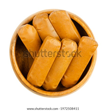 Vegan mini weenies, in a wooden bowl. Six small smoked sausages, made of saitan, a wheat gluten. Also called Wiener or Frankfurter Wuerstl. Close-up, from above, isolated over white, macro food photo. Stock photo ©