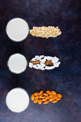 Vegan non dairy alternative milk. Coconut, almond, oat homemade milk on dark background. Different types of non-dairy milk. Healthy drinks concept. Top view. Copy space