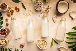 Vegan non dairy plant based milk in bottles and ingredients on light background. Lactose free milk substitute. Top view.