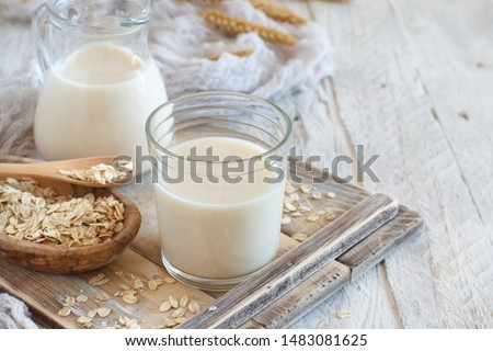 Vegan oat milk, non dairy alternative milk in a glass close up