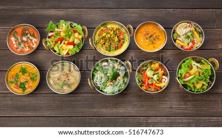 Photo of  Vegan or vegetarian restaurant dishes top view, hot spicy indian soups, rice and salads in copper bowls. Traditional indian cuisine meal assortment on wood background. Healthy eastern local food
