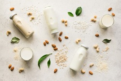 Vegan plant based milk and ingredients, top view, copy space. Various dairy free, lactose free nut and grains milk, substitute drink, healthy eating.