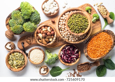Vegan protein source. Beans, lentils, nuts, broccoli spinach and seeds. Top view on white table. Healthy vegetarian food.
