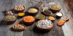Vegan protein source.Various assortment of legumes, lentils, chickpea and beans assortment in different bowls on wooden table. Top view.