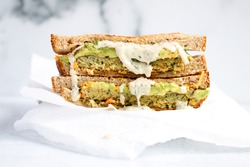 Vegan Ranch Dressing drizzled in a veggie burger sandwich - white background - straight on