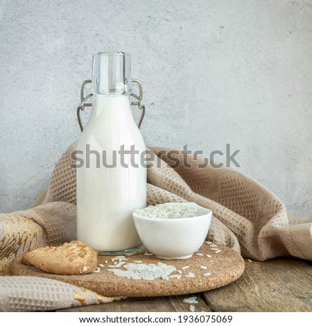 Vegan rice  milk and bowl with a rice  .Non dairy , alternative milk. Healthy vegetarian food and drink concept. Copy space . A bottle of rice milk and raw rice on a wooden table  and a napkin .