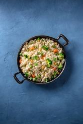 Vegan rice with vegetables, broccoli, carrot and grean peas, shot from above on a blue background with a place for text