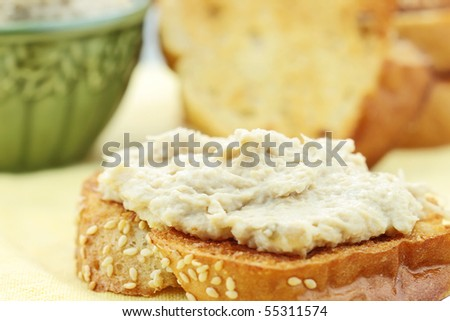 Vegan sandwich spread made with a meat substitute for shredded chicken or turkey and tofu mayonnaise. More spread and bread in background.