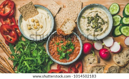 Vegan snack board. Flat-lay of various Vegetarian dips hummus, babaganush and muhammara with crackers, bread and fresh vegetables, wooden background, top view. Clean eating, dieting food concept