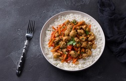 Vegan stew soy meat and vegetables served with boiled rice and greens on black textured background. delicious healthy diet food