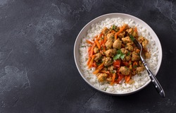 Vegan stew soy meat and vegetables served with boiled rice and greens on black textured background. delicious healthy diet food. space, top view