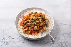 Vegan stew soy meat and vegetables served with boiled rice and greens on light gray textured background. delicious healthy diet food