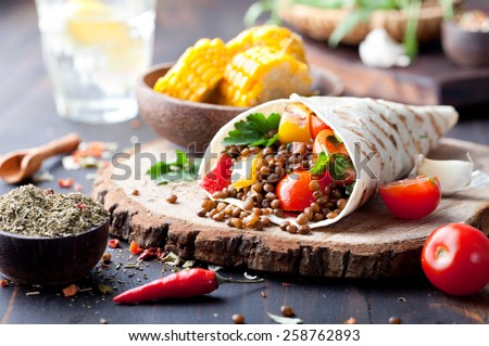Vegan tortilla wrap, roll with grilled vegetables and lentil  and boiled corn cob on a wooden background