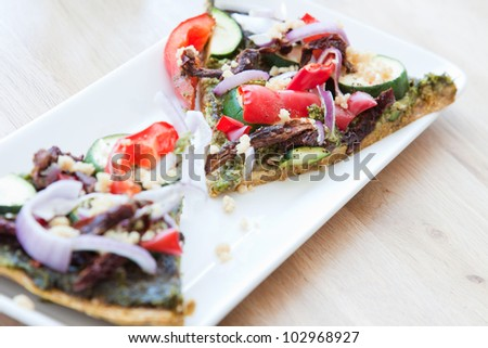 Vegan version of pizza served on a sprouted buckwheat & flax seed crust with cashew nut cheese & tomato marinara sauce.