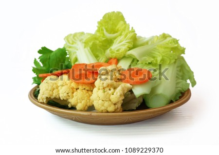 Vegatables set - diet food for health: green sweet basil (Thai basil), Celery (Smallage), morning glory, cauliflower, Chinese cabbages and orange carrots on plate isolated on white background