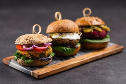 Vege burgers with carrots, beetroots and mushrooms. Front view. Black background.