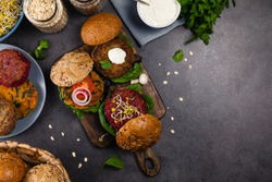 Vege burgers with carrots, beetroots and mushrooms. Top view. Black background.