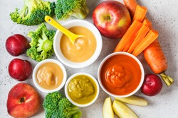 Vegetable and fruit baby puree (apple, broccoli, carrot, plum) in white bowl with ingredients. Baby food concept.