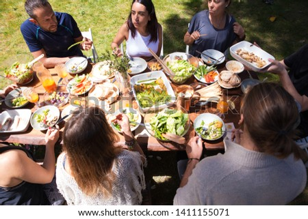 Vegetable and fruit snacks on table and eating people. Young men and women having meal together outdoors. Outdoor party concept