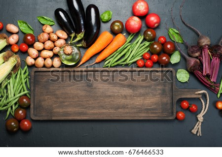 Vegetable background. A long brown wooden board, next to which lie fresh juicy organic vegetables, such as eggplants, carrots, tomatoes, asparagus beans, potatoes, beets etc, against a dark background #676466533