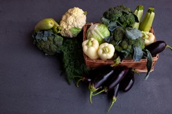 Vegetable basket. Fresh vegetables on the table black background. Set of food delivery box. Broccoli, cabbage, eggplant, white cabbage, cucumber, dill, cauliflower. Stilllife top view. Copy space.