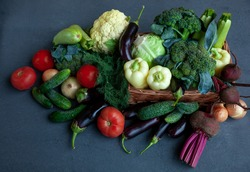 Vegetable basket. Fresh vegetables on the table black background. Set of food delivery box. Broccoli, cabbage, eggplant, white cabbage, cucumber, dill, cauliflower. Stilllife top view.