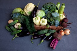 Vegetable basket from local market. Fresh vegetables on the table black background. Set of food delivery box. Broccoli, cabbage, eggplant, white cabbage, cucumber, dill, cauliflower. Stilllife
