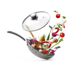 Vegetable composition. Frying pan with lid and flying vegetables, isolated on white background