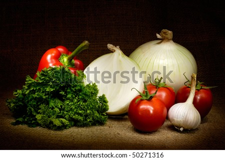 Vegetable country-style still life with tomatoes, onion, bell pepper, parsley and garlic on burlap background