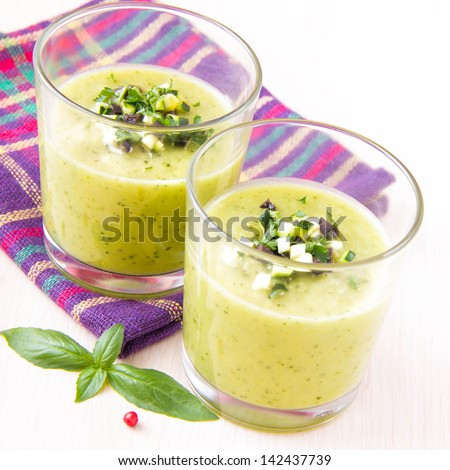 Vegetable cream soup with avocado, herbs, zucchini and black olives in glasses as an appetizer