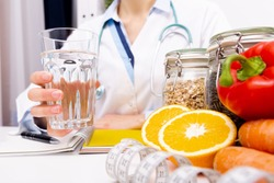 Vegetable diet nutrition and medication concept. Nutritionist offers healthy vegetables diet and drink water