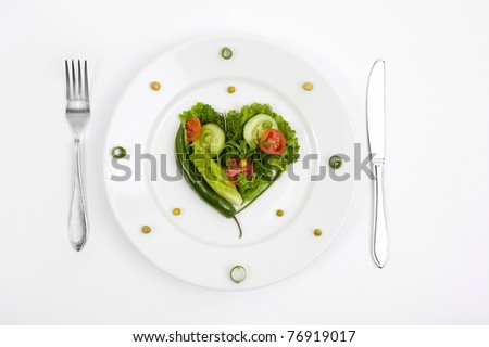 Vegetable dietary composition in the form of heart on a white plate with a plug and a knife.