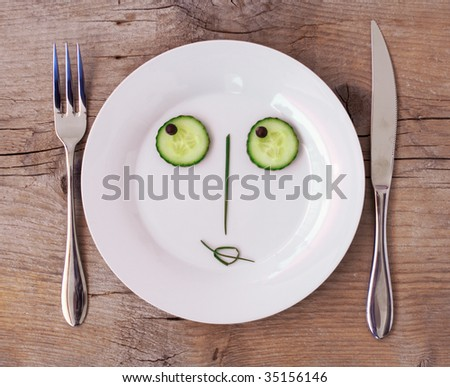 Vegetable Face on Plate with knife and fork, set on wooden board - Female, Flirting