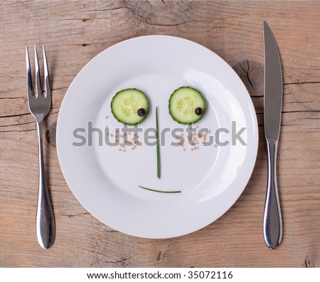 Vegetable Face on Plate with knife and fork, set on wooden board - Male, Shy