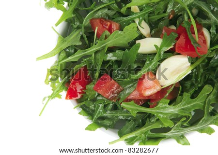 vegetable food : green salad with raw tomato and garlic in white bowl isolated over white background - stock photo