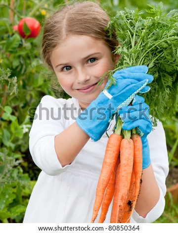 Vegetable garden - little gardener with bunch of organic carrots