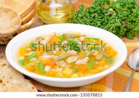vegetable minestrone with white beans and toast horizontal closeup
